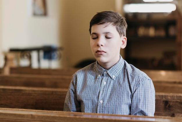 Kleine jongen bidden in de kerk met zijn ogen dicht Gratis Foto