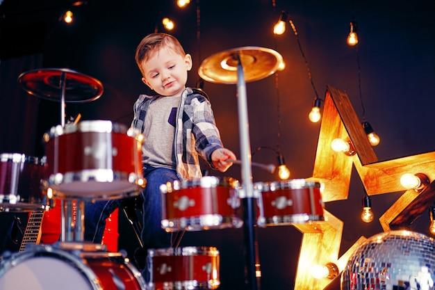 Kleine jongen drummen op het podium Premium Foto