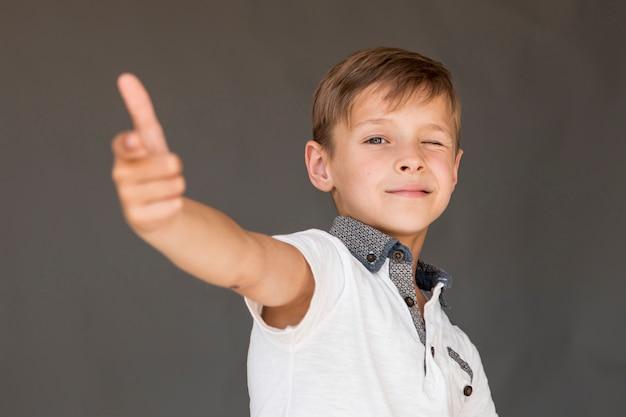 Kleine jongen een pistool met zijn vingers maken Gratis Foto