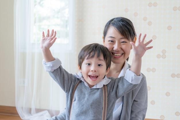 Kleine jongen en jonge moeder lacht en speelt samen Gratis Foto