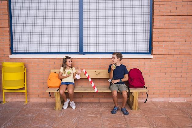 Kleine jongen en meisje die een appel eten tijdens de pauze zittend op een bankje sociale afstand houden. terug naar school tijdens covid pandemic. Premium Foto