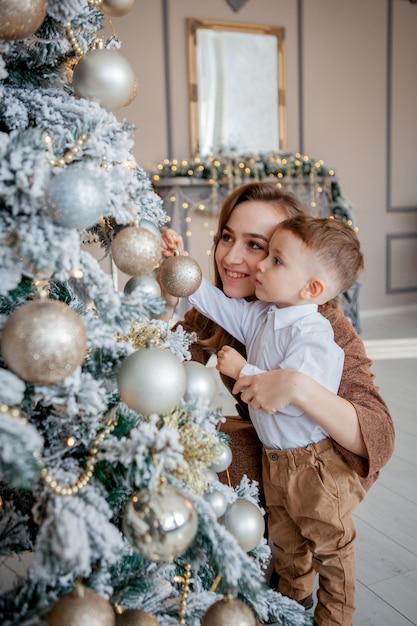 Kleine jongen en moeder siert een kerstboom voor kerstmis Premium Foto