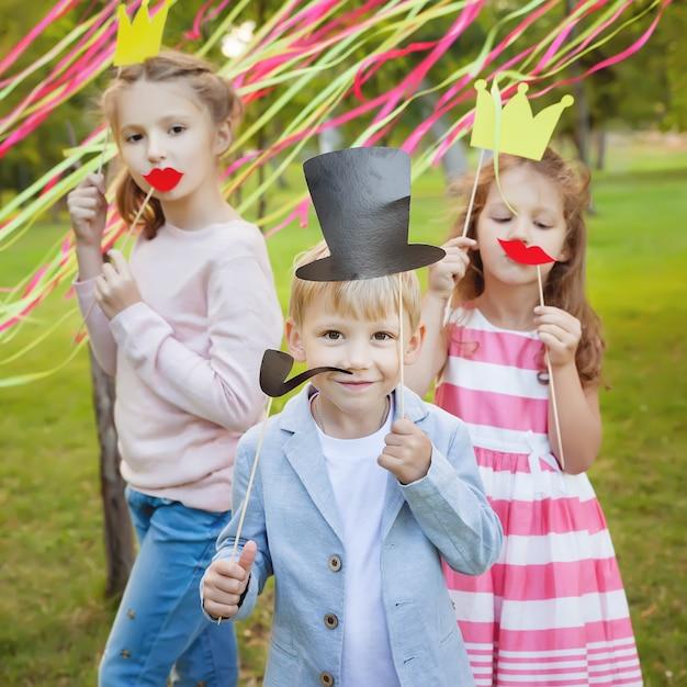 Kleine jongen en twee meisjes poseren met papieren maskers op een verjaardagsfeestje Premium Foto