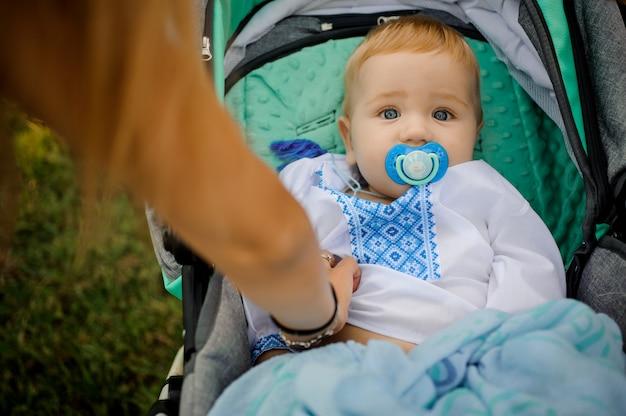 Kleine jongen gekleed in het geborduurde shirt liggend in de kinderwagen met een fopspeen Premium Foto