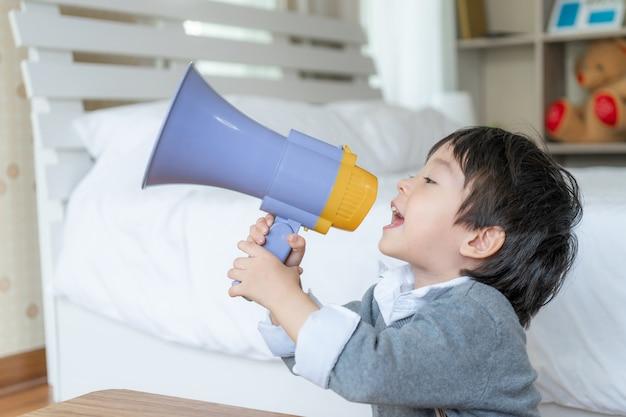 Kleine jongen geniet van praten met megafoon Gratis Foto