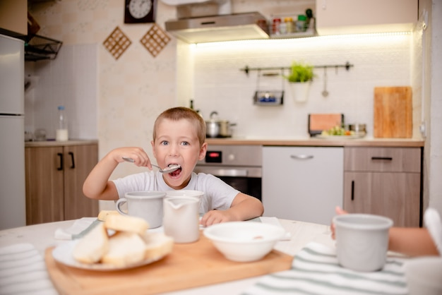 Kleine jongen heeft ontbijt. lichte keuken, houten tafel en keukenpersoneel Premium Foto
