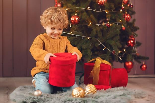 Kleine jongen in de buurt van de kerstboom in een bruine trui Gratis Foto