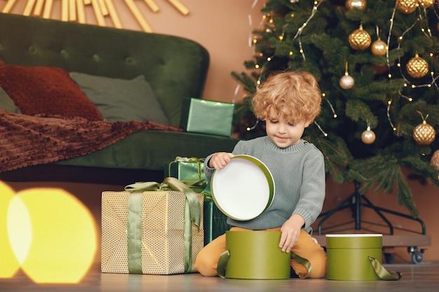 Kleine jongen in de buurt van de kerstboom in een grijze trui Gratis Foto