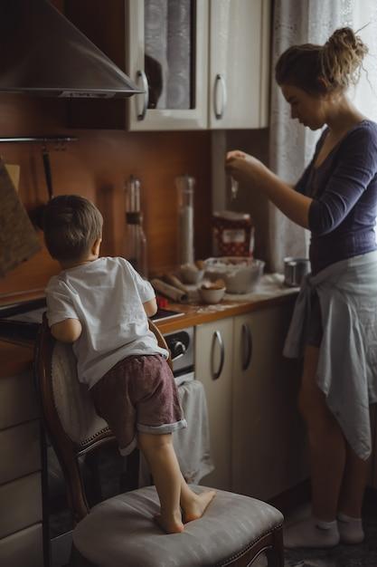 Kleine jongen in de keuken helpt moeder om te koken. het kind is betrokken bij het koken. Gratis Foto