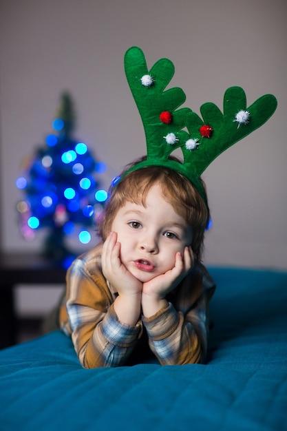 Kleine jongen in een nieuwjaarskostuum van een hert dat kerstmis en nieuwjaar viert Premium Foto