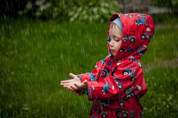 Kleine jongen in een waterdichte jas in tractoren vangen de regen. kind plezier buitenshuis in zomer douche Premium Foto