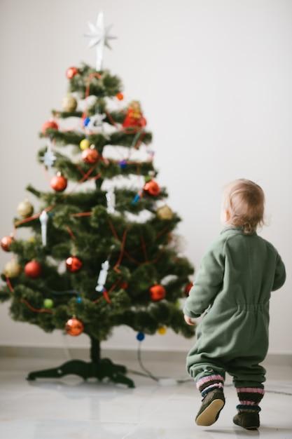 Kleine jongen in groene springers loopt naar kerstboom Gratis Foto