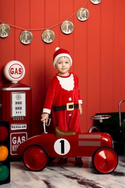 Kleine jongen in santa claus kostuum rijdt op een rode speelgoedauto. gelukkige jeugd. kerstavond. Premium Foto