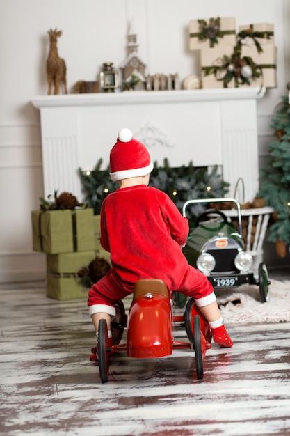 Kleine jongen in santa claus kostuum rijdt op een rode speelgoedauto Premium Foto