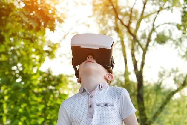 Kleine jongen in virtuele realiteit helm op te zoeken Premium Foto