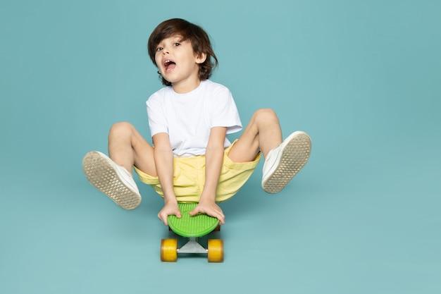 Kleine jongen jongen in wit t-shirt skateboard rijden op blauwe muur Gratis Foto