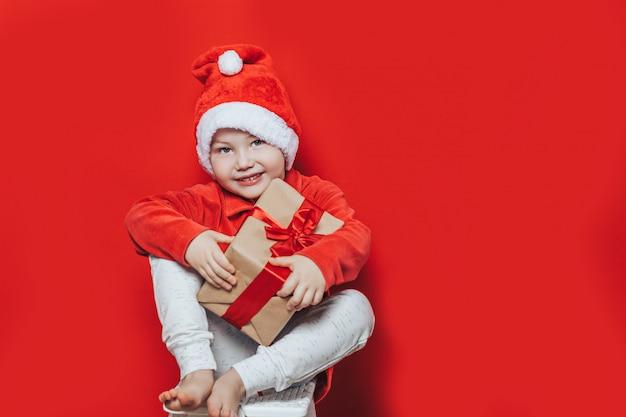 Kleine jongen kerstcadeau te houden Premium Foto