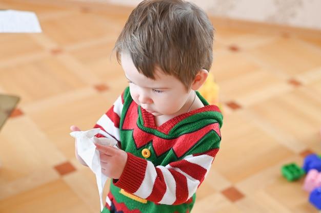 Kleine jongen met donker haar die een tissue gebruikt om zijn neus te reinigen van verkoudheid of pollenallergieën. Premium Foto