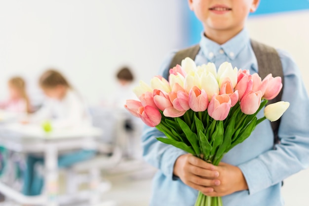 Kleine jongen met een boeket bloemen voor zijn leraar Premium Foto