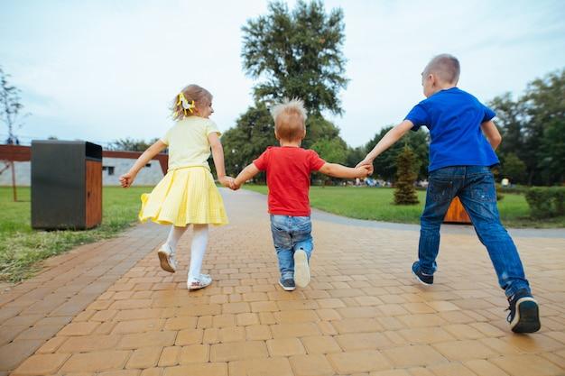 Kleine jongen met een meisje in park wandelen in de zomer in zonnige dag. kleine vrienden houden buitenshuis handen vast. gelukkige jeugd. de emotionele kinderen lopen in de open lucht. broer en zus spelen in de natuur Premium Foto
