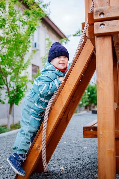 Kleine jongen met het syndroom van down speelt op de speelplaats, selectieve aandacht Premium Foto