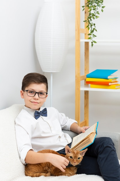 Kleine jongen met kat lezen Gratis Foto