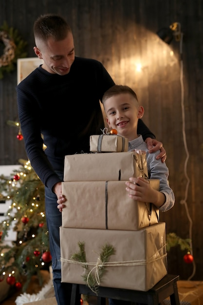 Kleine jongen met kerstcadeautjes Gratis Foto