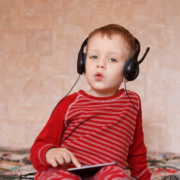 Kleine jongen met koptelefoon luisteren naar muziek en zingen Premium Foto