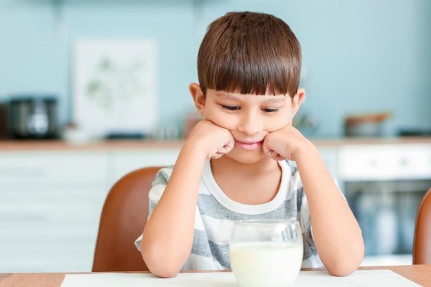 Kleine jongen met melk in de keuken Premium Foto