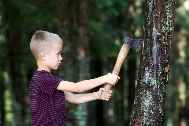 Kleine jongen met zware oude scherpe de boomtrump van de ijzerbijl in bos op de zomerdag. buitenactiviteiten en fysieke arbeid. Premium Foto