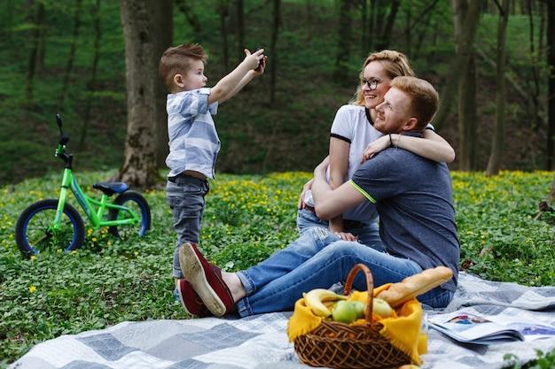 Kleine jongen neemt een foto van zijn ouders op de smartphone tijdens een picknick in het park Gratis Foto