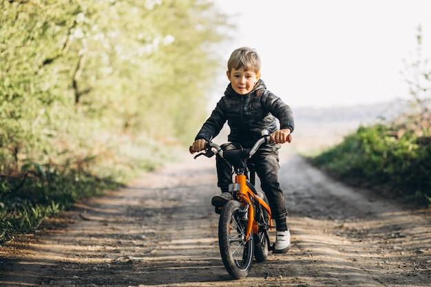 Kleine jongen op fiets in park Gratis Foto
