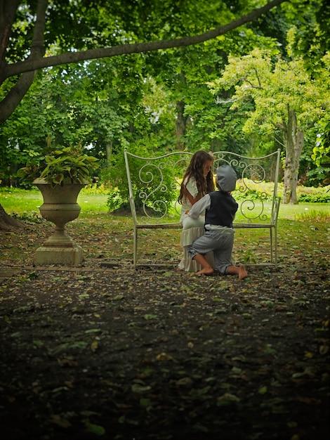 Kleine jongen op zijn knieën voor een klein meisje in een tuin omgeven door groen Gratis Foto
