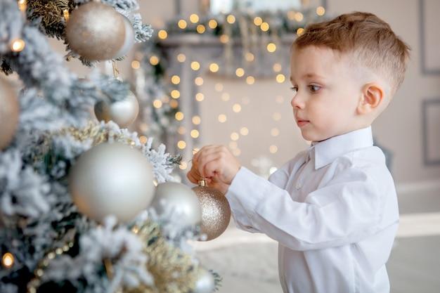 Kleine jongen siert een kerstboom voor kerstmis Premium Foto