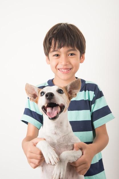 Kleine jongen speelt met zijn vriend hond jack russel Premium Foto