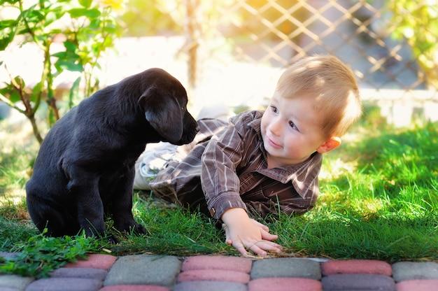 Kleine jongen spelen in de tuin met een puppy labrador Premium Foto