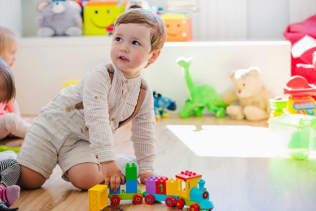 Kleine jongen spelen met trein speelgoed Gratis Foto