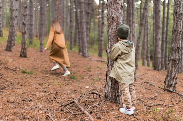 Kleine jongen verbergen van zijn moeder in het bos Gratis Foto