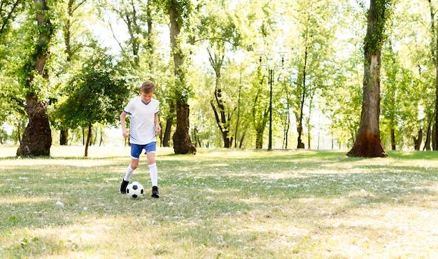 Kleine jongen voetballen alleen met kopie ruimte Gratis Foto