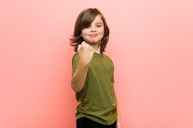Kleine jongen vuist tonen aan camera, agressieve gelaatsuitdrukking. Premium Foto