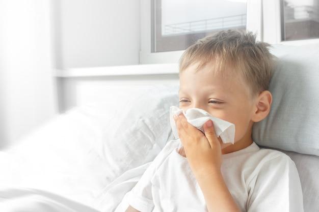 Kleine jongen ziek in bed met temperatuur. het kind werd verkouden. hij niest, hoest en heeft een loopneus. gezondheidszorg, griep, hygiëne. Premium Foto
