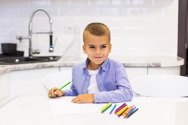Kleine jongen zit aan een tafel in een lichte keuken en tekent met potloden Gratis Foto
