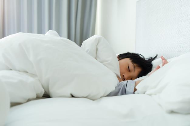 Kleine jongensslaap op bed bij slaapkamer Premium Foto