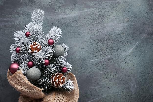 Kleine kerstboom in jute versierd met rode kerstballen en bessen op donker Premium Foto