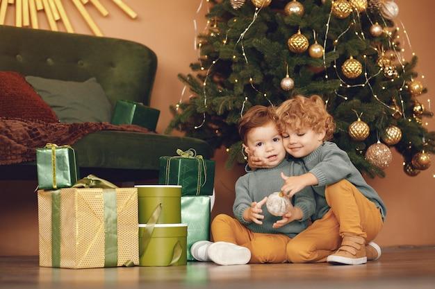 Kleine kinderen in de buurt van de kerstboom in een grijze trui Gratis Foto