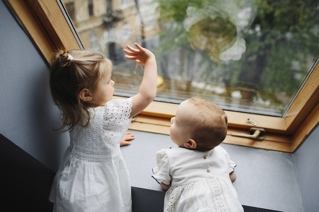 Kleine kinderen kijken uit het raam Gratis Foto