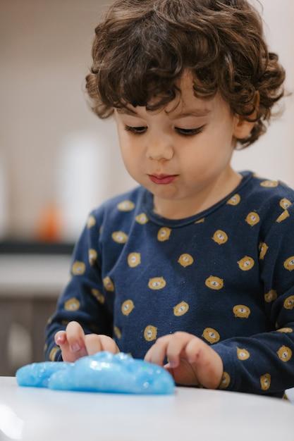 Kleine kinky jongen die met slijm in zijn kamer speelt Premium Foto