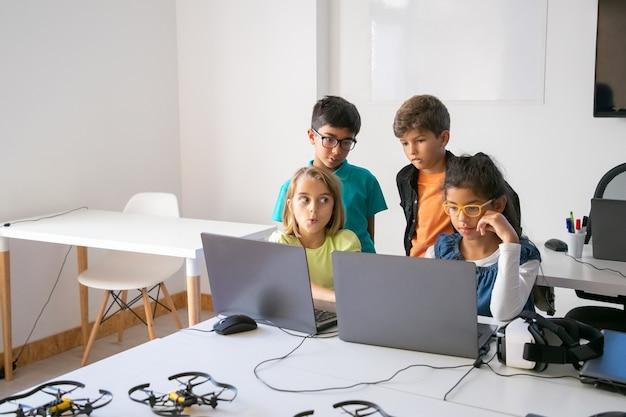 Kleine klasgenoten doen groepstaken, gebruiken laptops en studeren op een computerschool Gratis Foto