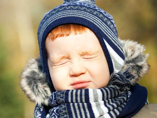 Kleine knappe jongen met gesloten ogen in herfst park, close-up foto, kind heeft rode haarkleur Premium Foto