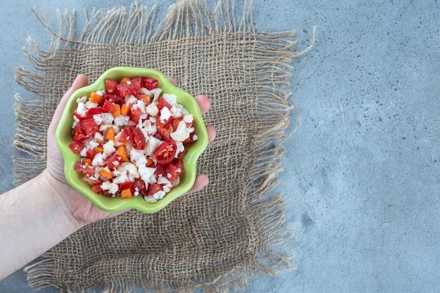 Kleine kom in palm, gevuld met bloemkool en pepersalade op marmeren tafel. Gratis Foto